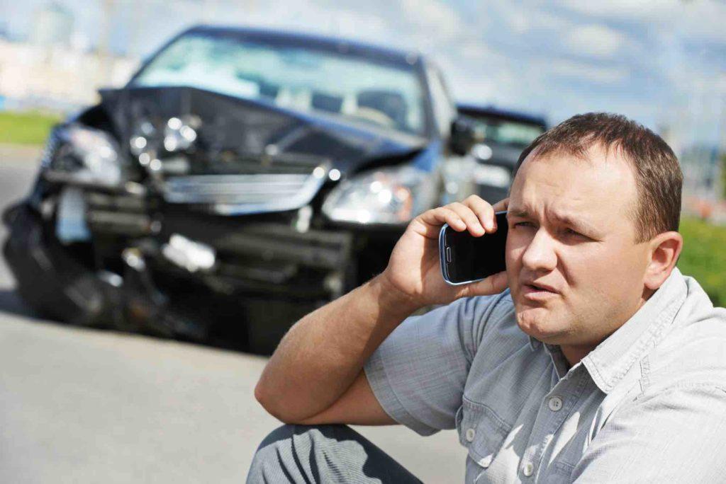 Mann telefoniert vor einem Auto mit Totalschaden
